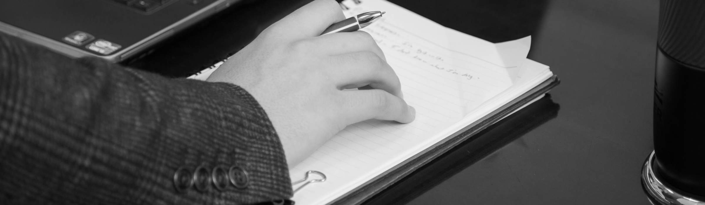 A person holding a pen resting their hand on a notebook
